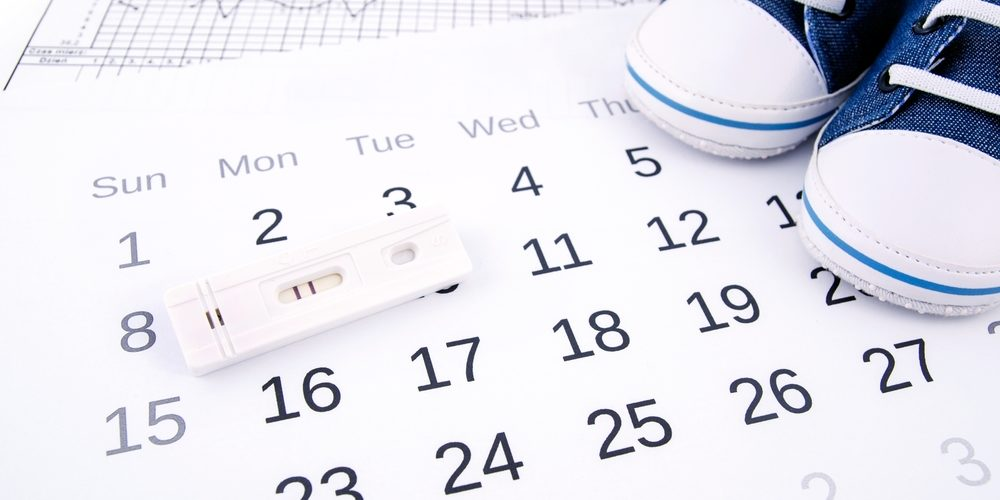Pregnancy Test On Calendar And Baby Shoes