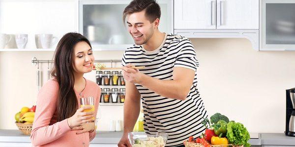 man kookt voor zwangere vrouw